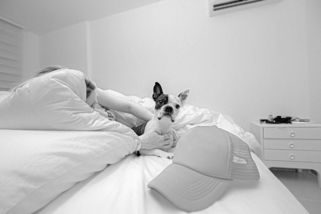 grayscale photo of woman lying on bed beside dog